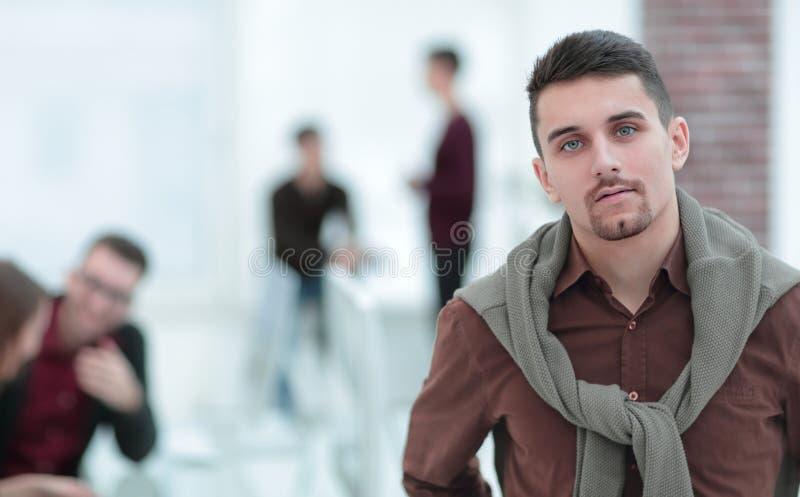 确信的年轻人在办公室的背景中 免版税库存图片