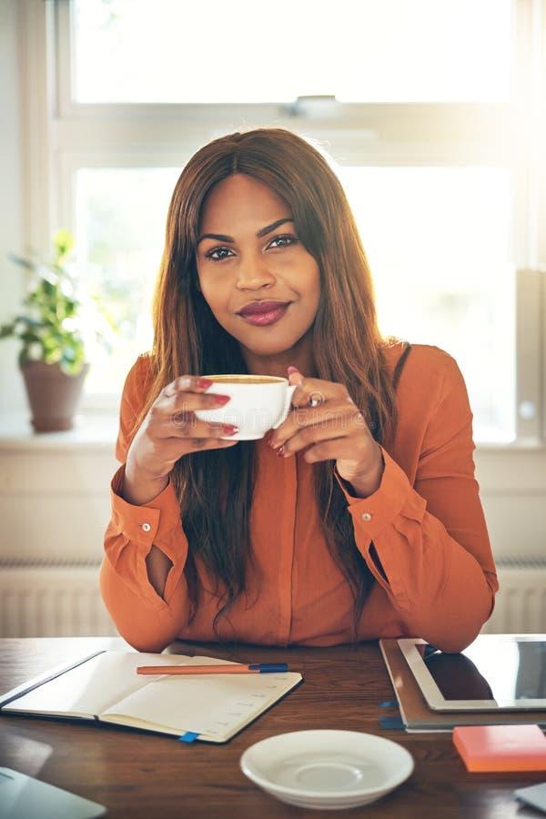 确信的年轻女性企业家饮用的咖啡,当workin时 免版税库存图片