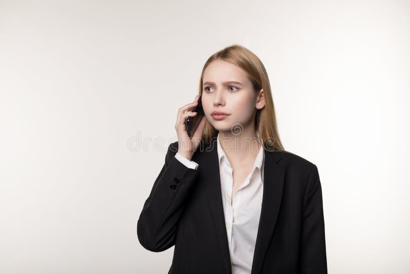 确信的年轻白肤金发的女实业家谈话在手机,在白色背景,与事务沟通 库存图片