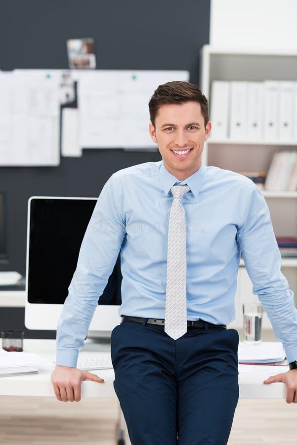 确信的微笑的商人在他的办公室 库存图片