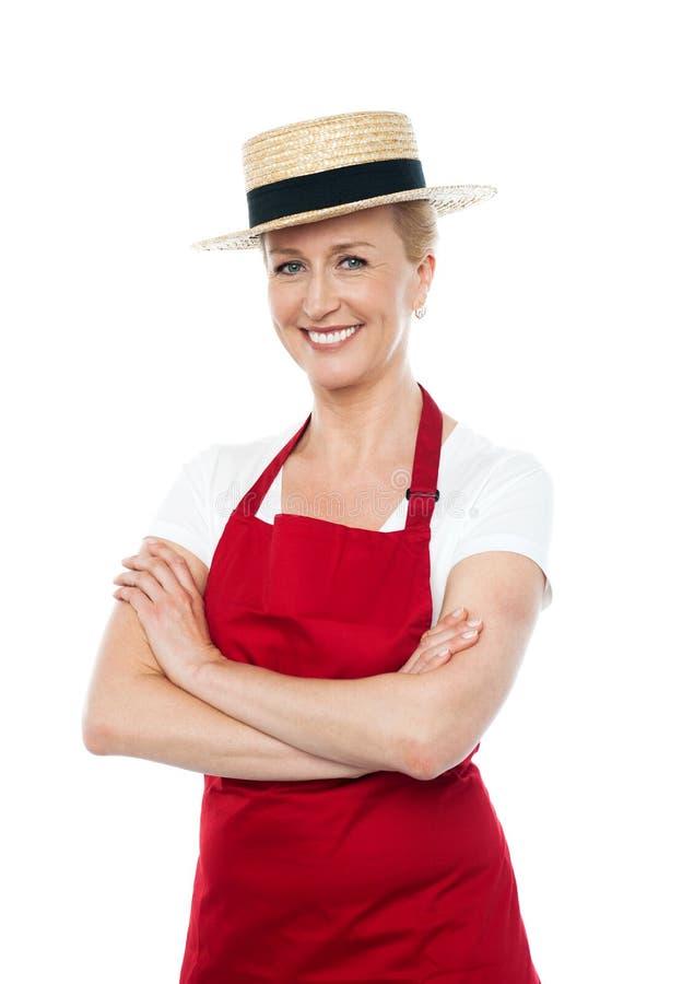 确信的快乐的女性厨师佩带的帽子 免版税图库摄影