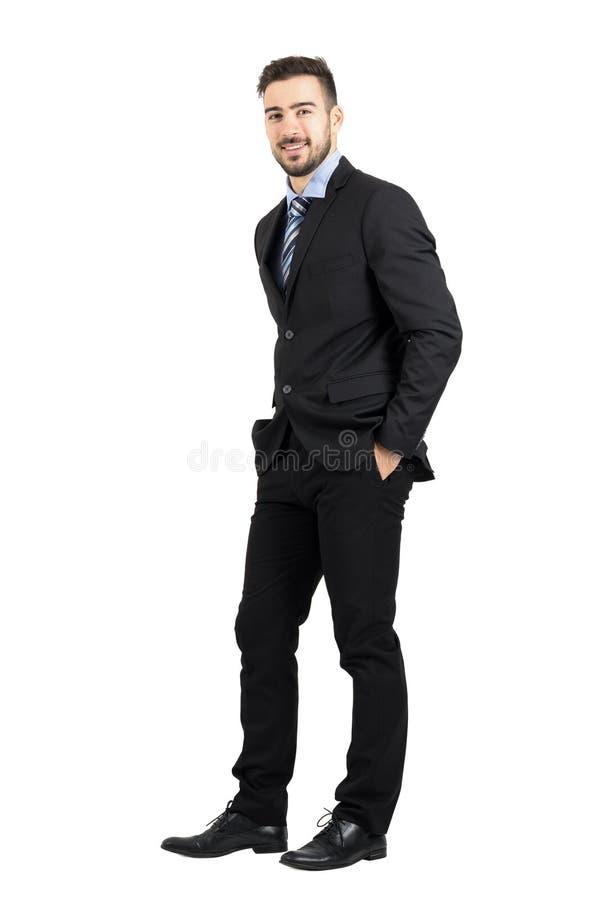 确信的愉快的商人用在口袋侧视图的手 免版税库存照片