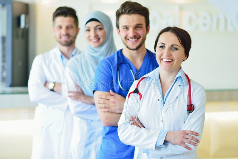确信的愉快的小组画象站立在医疗办公室的医生 免版税图库摄影
