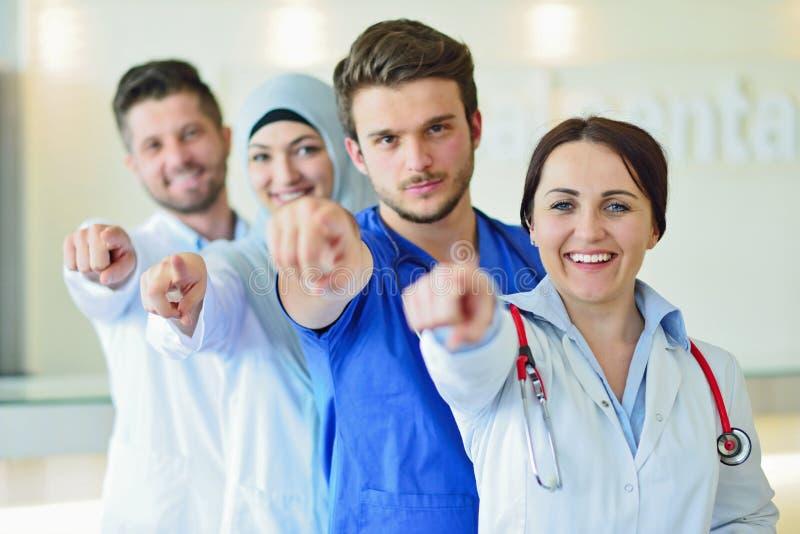 确信的愉快的小组画象站立在医疗办公室的医生 免版税库存照片