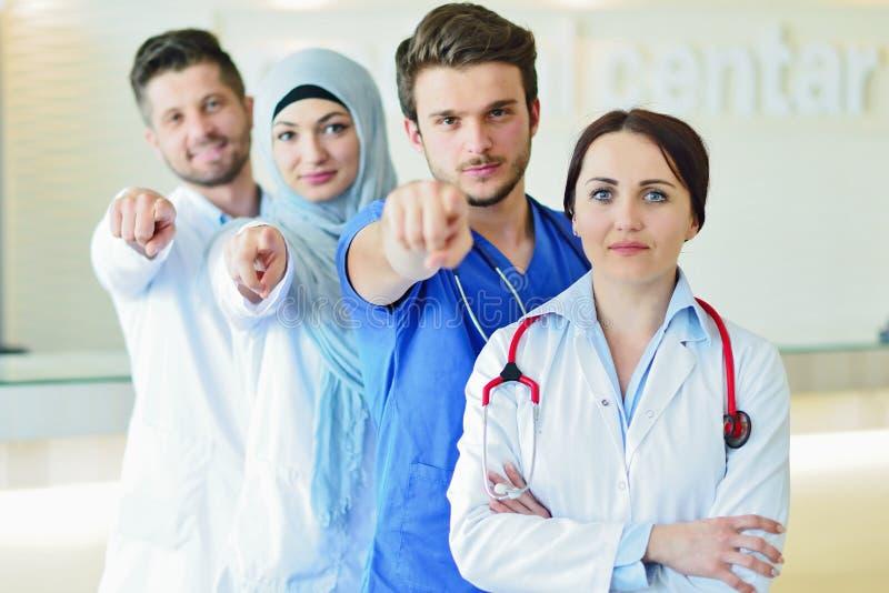确信的愉快的小组画象站立在医疗办公室的医生 库存照片