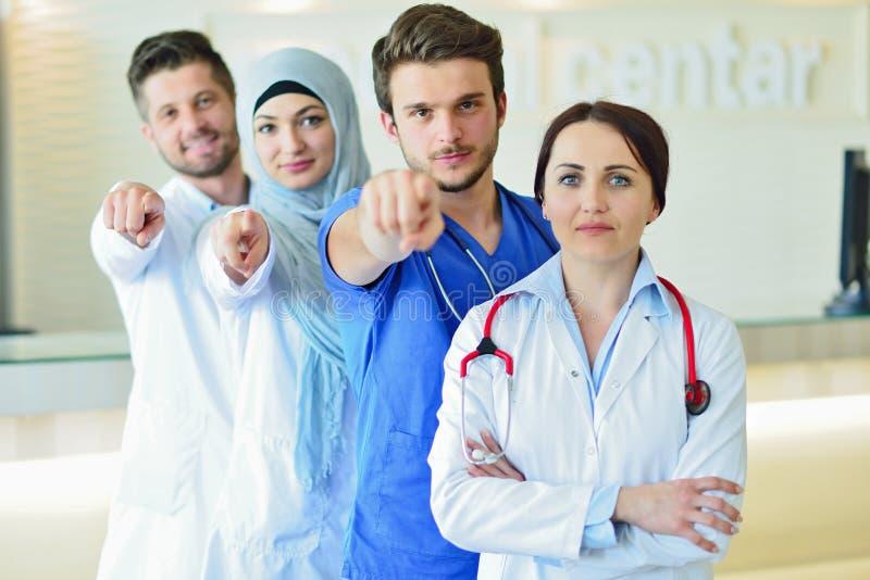 确信的愉快的小组画象站立在医疗办公室的医生 免版税库存图片