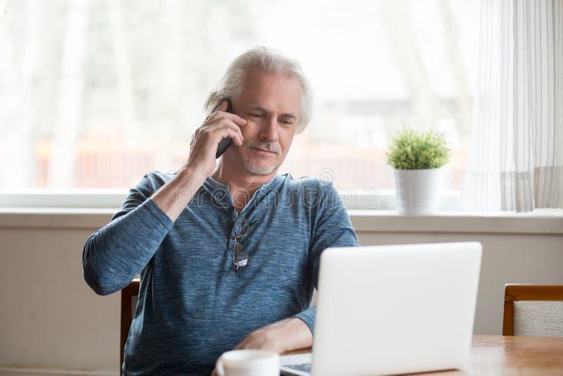确信的成熟人在谈话的桌上坐电话 免版税库存图片