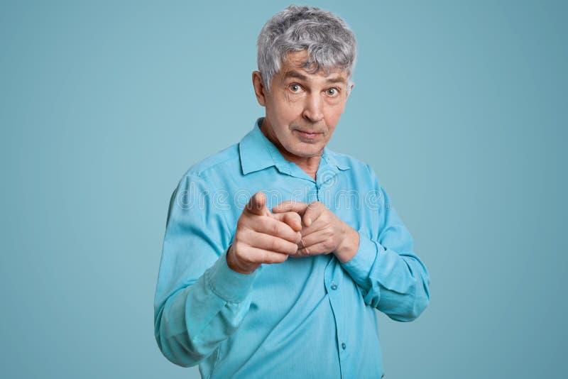 确信的成熟人领抚恤金者画象的腰部指向与两个食指照相机,穿戴在蓝色正式衬衣,姿势 库存照片