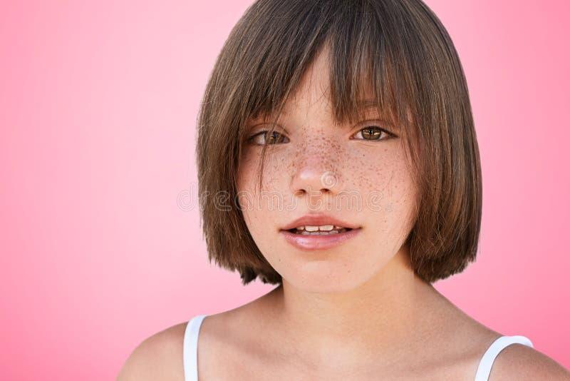 确信的有雀斑的美丽的小女孩室内射击有浮动的发型的在s看照相机,高兴被拍摄 免版税库存照片
