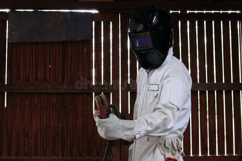 确信的焊工和在白色安全制服的防护盔甲画象有火炬的在工厂 行业概念 免版税库存图片