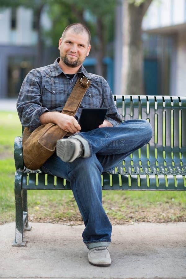 确信的男学生坐长凳在校园 免版税库存照片