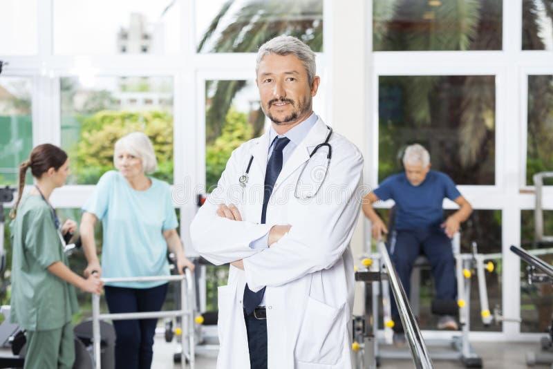 确信的男性在修复铈横渡的生理治疗师常设胳膊 免版税库存图片