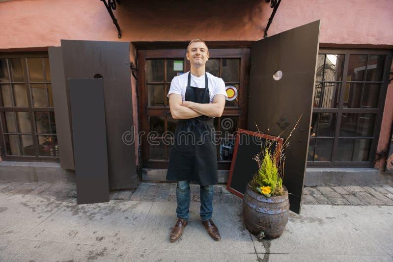 确信的男性推销员常设胳膊画象横渡了外部咖啡商店 库存照片