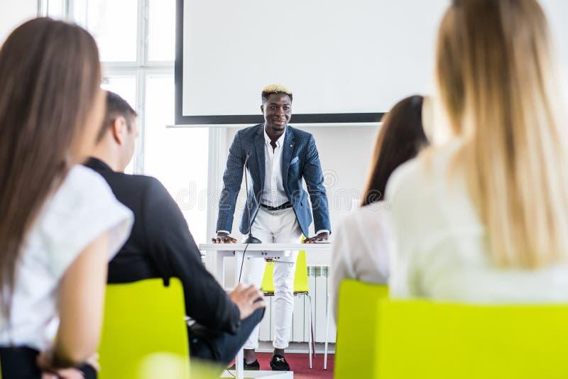确信的美国黑人的商人谈论与他的队在介绍 商业主持会议服务台查出在白色 企业生意人cmputer服务台膝上型计算机会议微笑的联系与使用妇女 库存图片