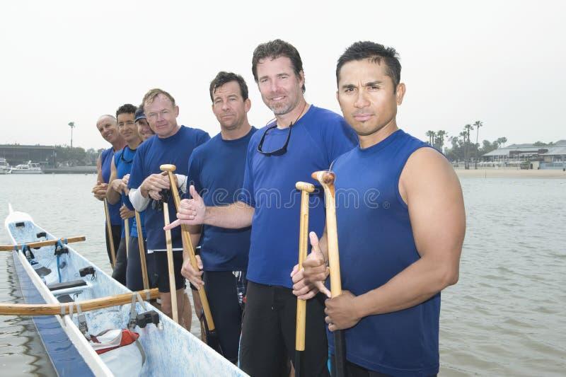 确信的舷外架乘独木舟的队 免版税图库摄影