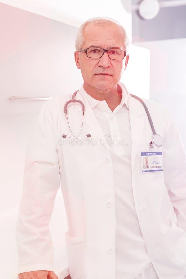 确信的资深医生画象站立在医院的labcoat的 免版税库存图片