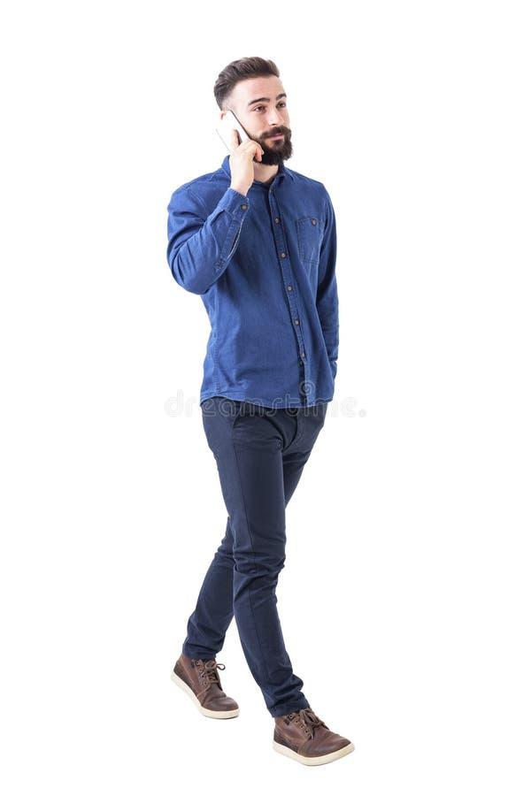 确信的轻松的年轻成年男性业务经理走和谈话在手机 免版税库存照片