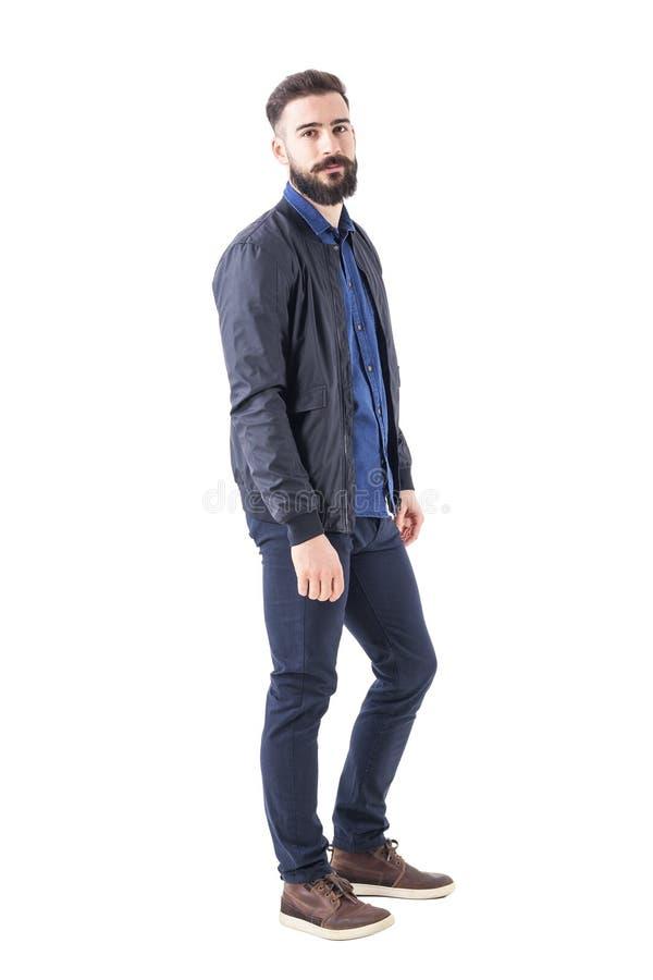 确信的轻松的强壮男子的人侧视图摆在和看照相机的短夹克的 库存照片