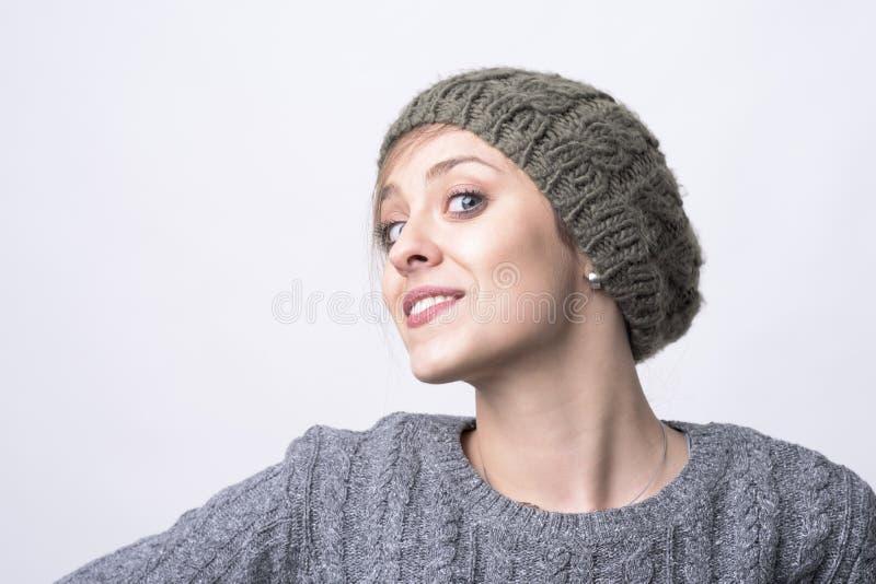 确信的迷人的年轻行家妇女画象有微笑被编织的盖帽的摆在和 免版税库存图片
