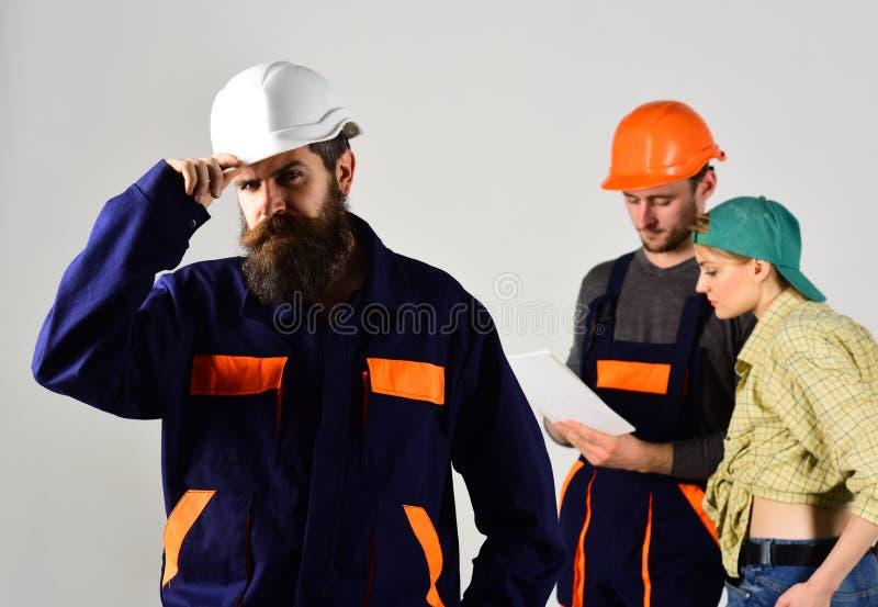 确信的队头 队上司固定安全帽,当人们谈论工程项目在背景时 营造商 免版税库存照片