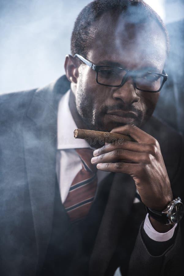 确信的非裔美国人的商人抽烟的雪茄 库存照片