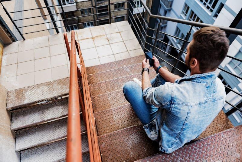 确信的年轻人坐有手机的台阶 免版税图库摄影