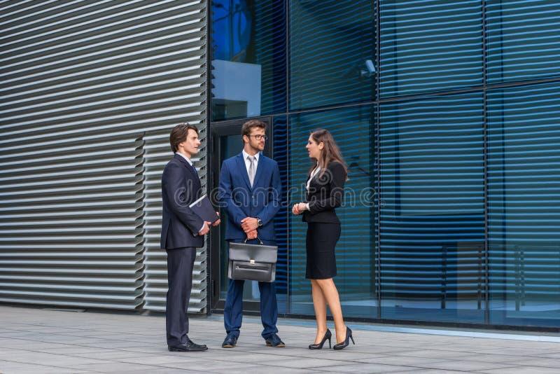 确信的businesspersons谈话在现代办公楼前面 商人和女实业家有事务 库存图片