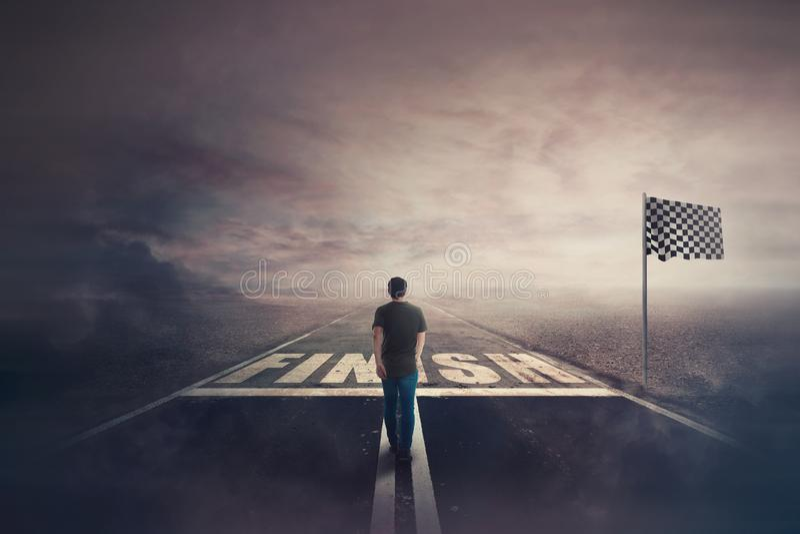确信竞争的年轻人走在沥青平交道口终点线 超现实的挑战赢得的概念, 库存照片