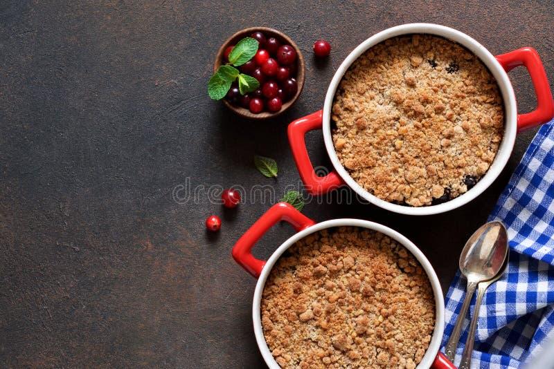 碎屑用蔓越桔和其他莓果,在厨房用桌上的坚果 o 库存照片
