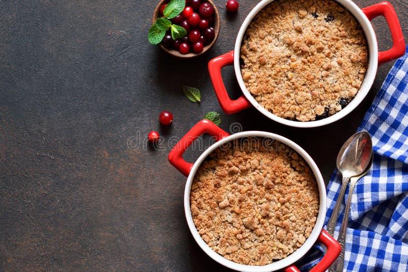 碎屑用蔓越桔和其他莓果,在厨房用桌上的坚果 免版税库存照片
