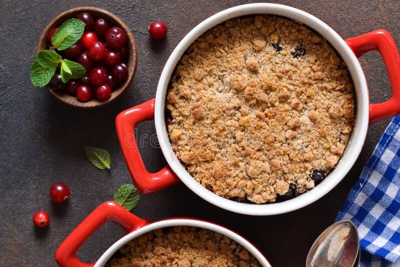 碎屑用蔓越桔和其他莓果,在厨房用桌上的坚果 库存照片
