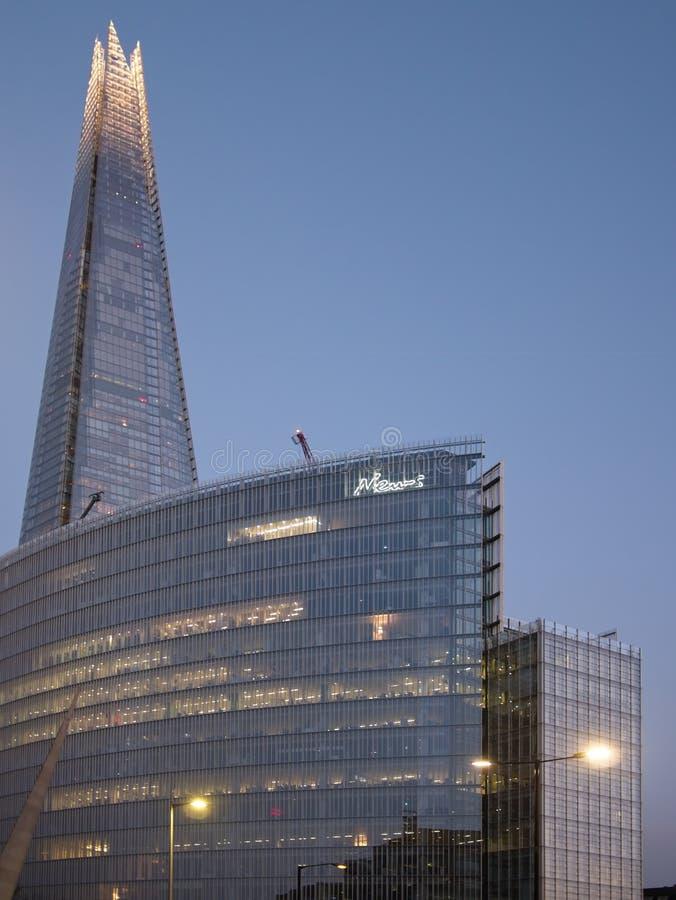 碎片和周围的现代玻璃大厦在黄昏 库存图片