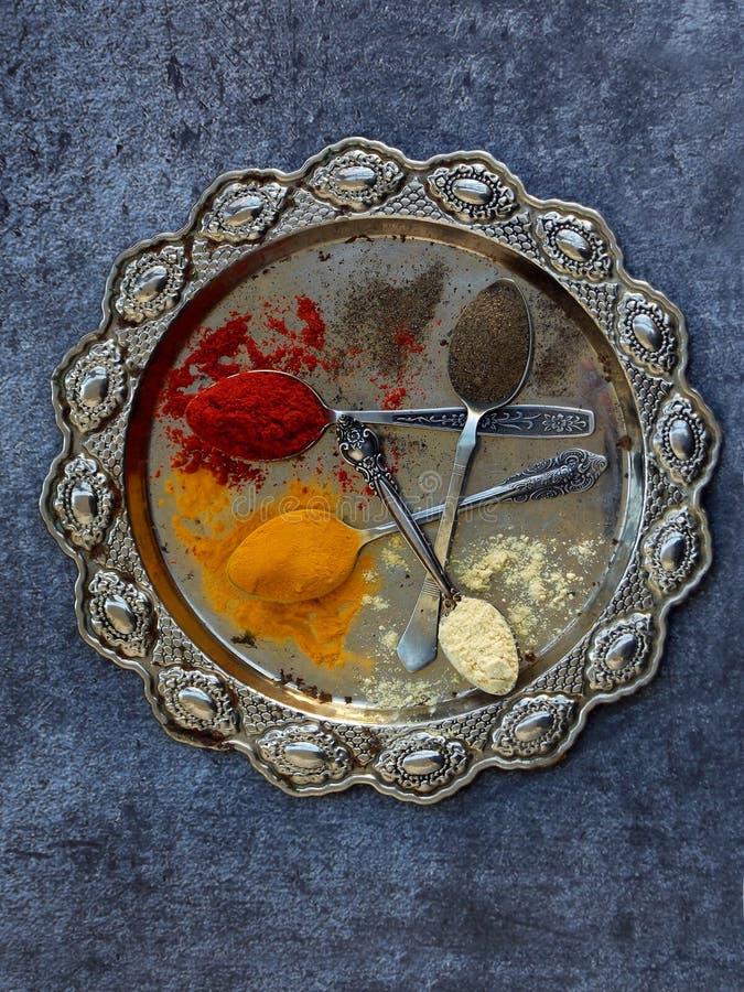碎香料的构成在一把匙子的在金属盘 辣椒粉,姜黄,姜,黑胡椒 顶视图 库存图片