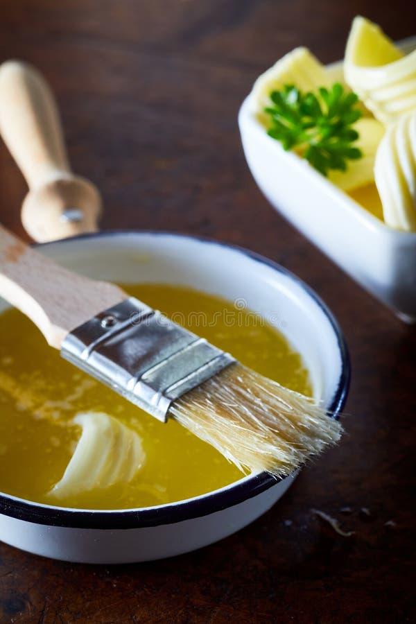 碗与一把涂抹的刷子的熔化黄油 免版税库存图片