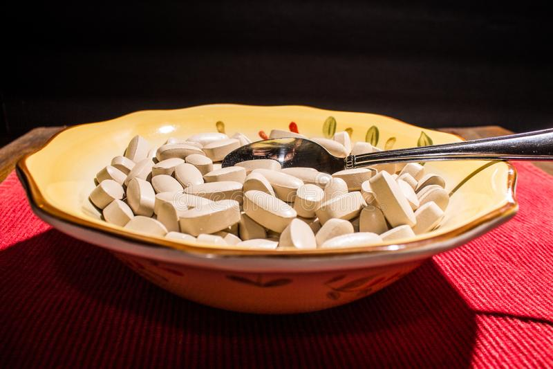 碗与匙子的药片 免版税库存照片