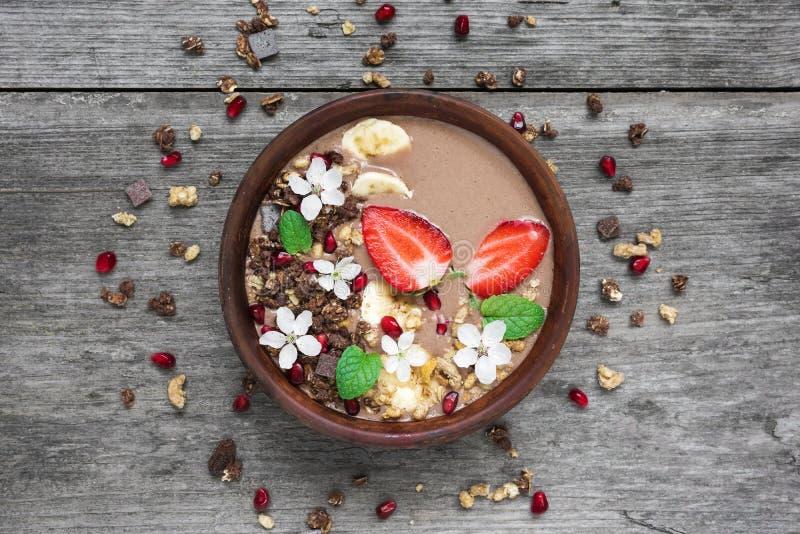 碗与巧克力格兰诺拉麦片、草莓和用花装饰的石榴种子的choclate和香蕉圆滑的人 库存图片