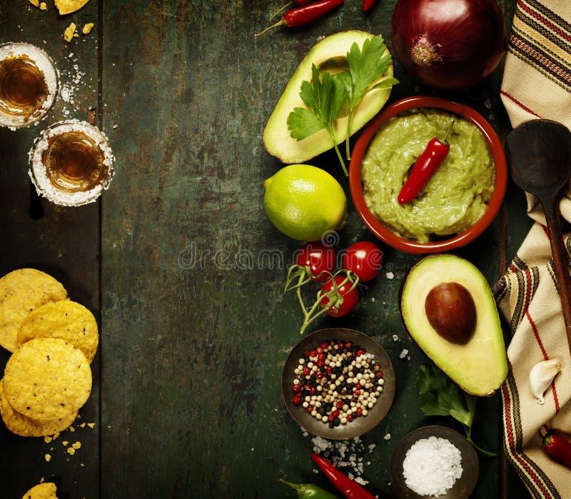 碗与新鲜的成份和龙舌兰酒射击的鳄梨调味酱捣碎的鳄梨酱 库存图片