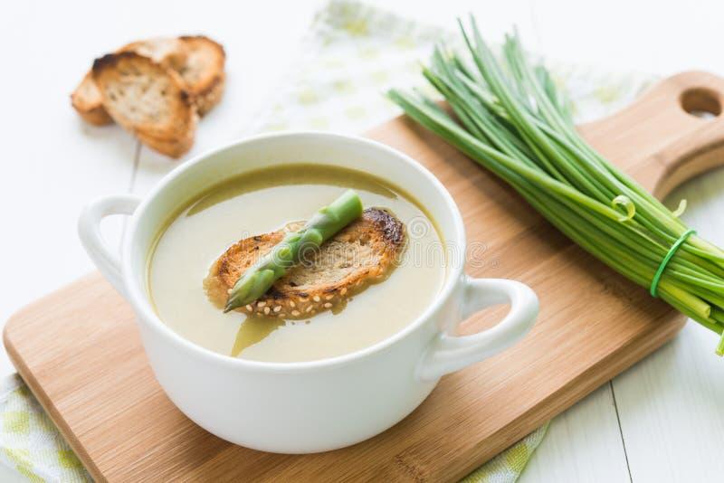 碗与芦笋矛和面包的芦笋汤在切口 库存照片