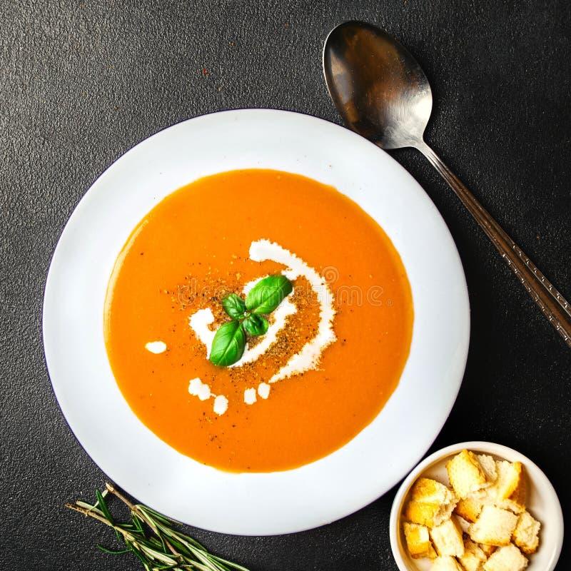 碗与蓬蒿叶子的南瓜汤在黑板岩桌上 新鲜 图库摄影