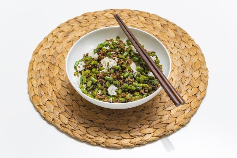 碗剁碎的牛肉用圆的豆和米,与筷子在秸杆席子 图库摄影