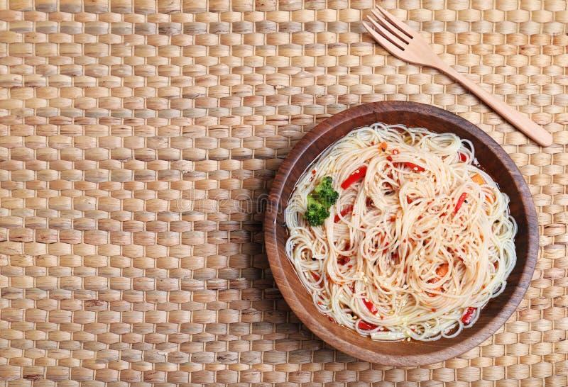 碗可口面条用汤和菜在柳条背景,顶视图 免版税图库摄影