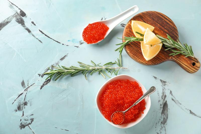 碗和匙子用可口红色鱼子酱在轻的桌上 免版税库存图片