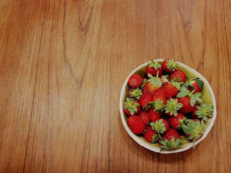 碗在一张木桌上的草莓:问候的完善的背景 免版税图库摄影