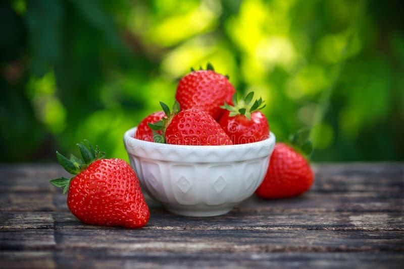 碗在木桌上的新鲜的草莓在夏天庭院里 库存图片