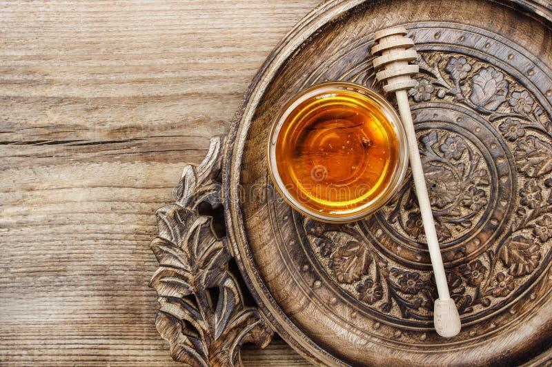 碗在木桌上的蜂蜜。健康生活的标志 免版税库存图片