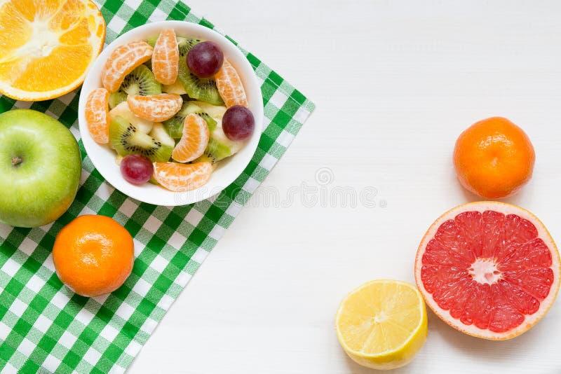 碗在白色木背景,顶视图,拷贝空间的健康新鲜水果沙拉 免版税图库摄影