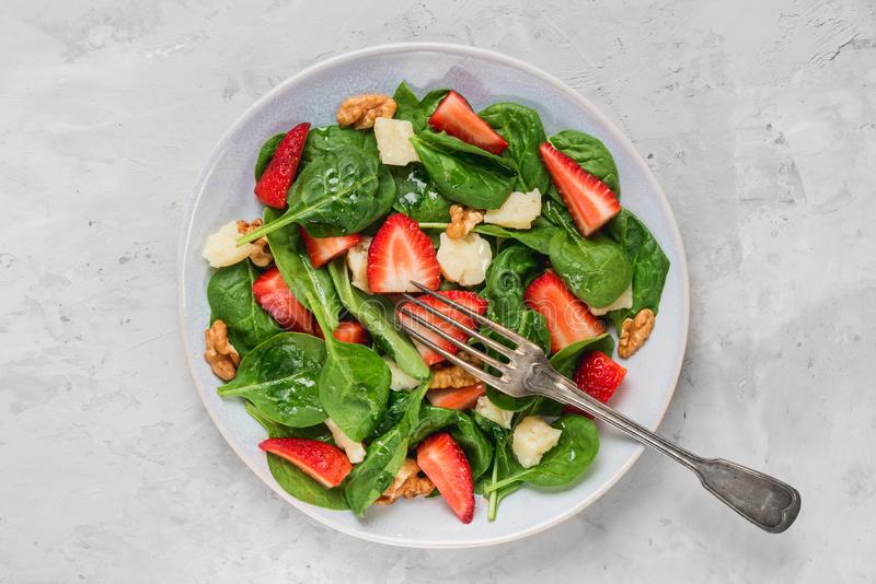 碗夏天菠菜沙拉用草莓、帕尔马干酪和核桃与一把叉子在具体背景 免版税图库摄影