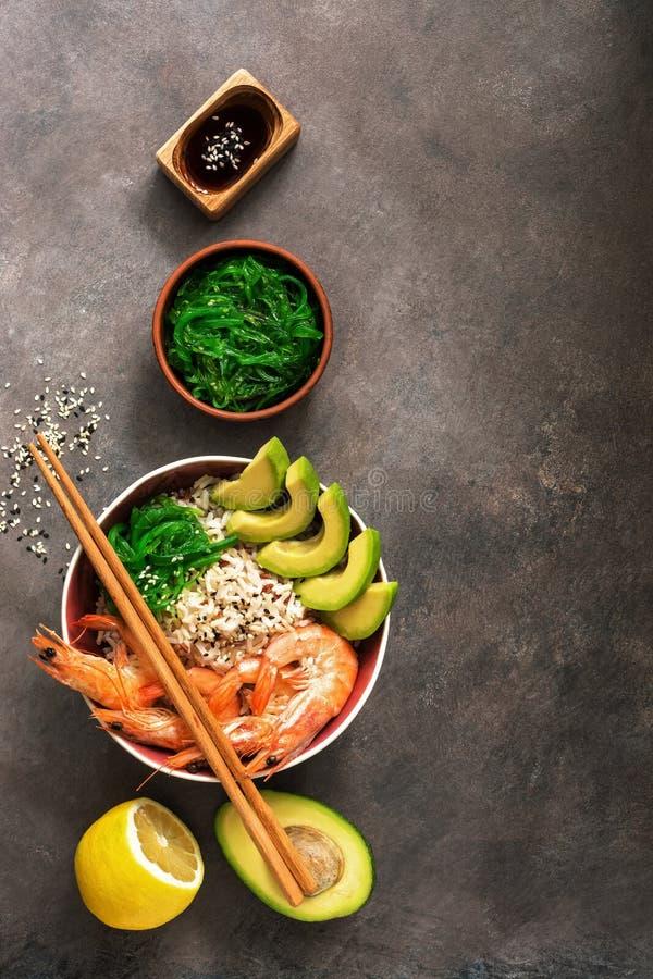 碗捅虾、米、鲕梨、chuka、筷子、酱油和芝麻在黑暗的土气背景 顶视图,平的位置,拷贝 库存图片
