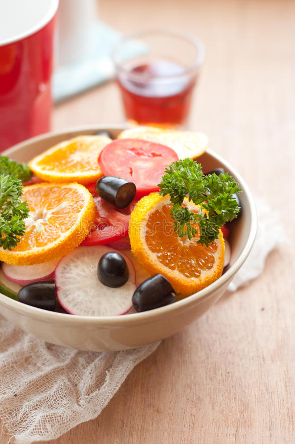碗新鲜的沙拉用蕃茄,桔子,葡萄 免版税库存照片