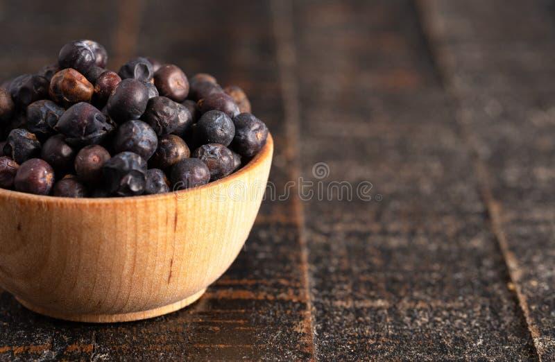 碗有很多在木表上的干杜松子 免版税图库摄影